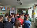 Uczniowie szkoły średniej słuchają prelekcji właścicielki szkoły językowej.
